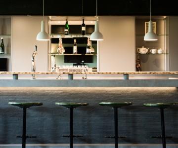 Lambrisering van schaaldelen en stoere betonlook bar in deze mancave