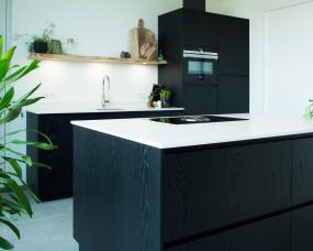 Gespoten eiken keuken met composiet werkblad en ingebouwde spots in eiken legplank