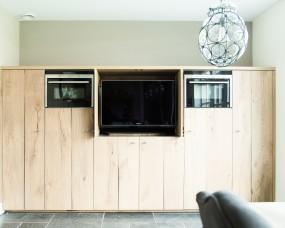 Bijkeuken wand voorzien van alle apparatuur met afsluitbare deuren voor TV